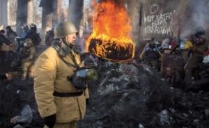 Припадник опозиције поред запаљених буради у центру Кијева